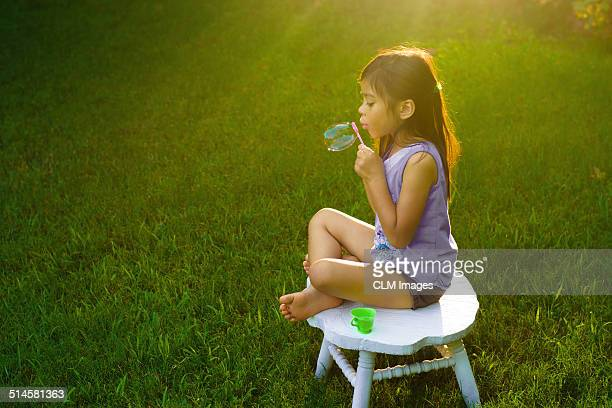 Little girl blowing bubbles at dusk