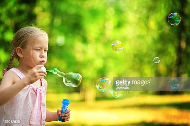 Petite fille souffle des bulles