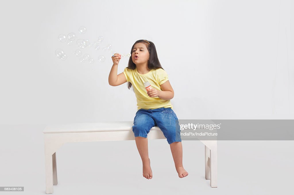 Little girl blowing bubbles : Stock Photo