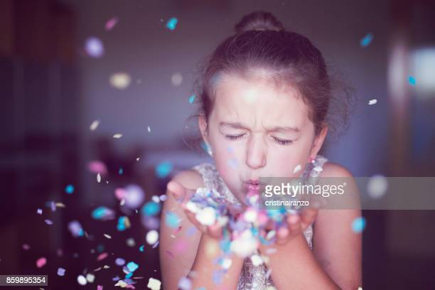 Little girl blowing confetti in her hands