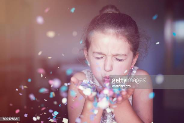 little girl blowing confetti in her hands - luck stock pictures, royalty-free photos & images