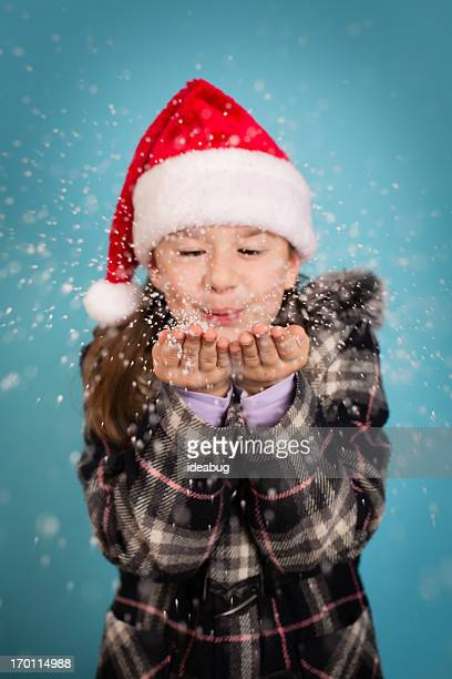97224f727d333 Little Girl Blowing Handful of Snow and Wearing Santa Hat