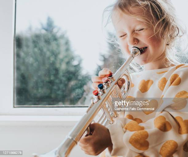 little girl blowing hard into a toy trumpet and giggling - wind instrument stock pictures, royalty-free photos & images
