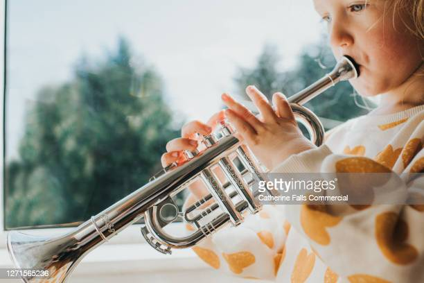 little girl blowing hard into a toy trumpet - human finger stock pictures, royalty-free photos & images