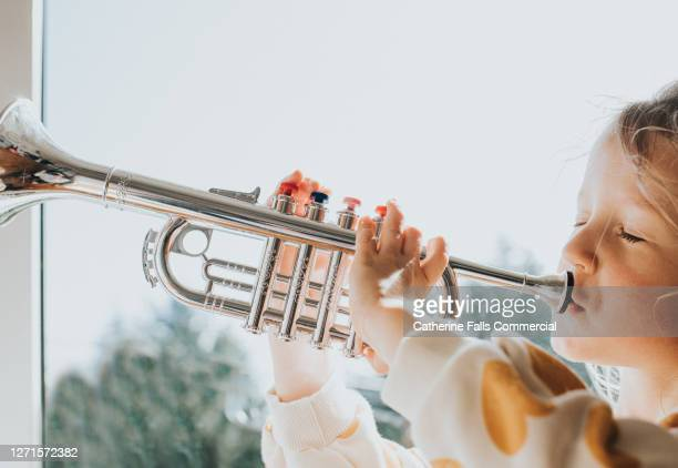 little girl blowing hard into a toy trumpet - wind instrument stock pictures, royalty-free photos & images
