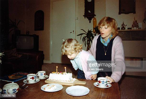 little girl blowing out birthday candles - happy birthday vintage stockfoto's en -beelden