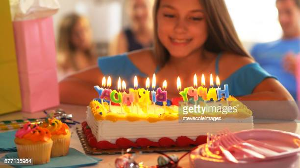 Little girl blowing out birthday candles.