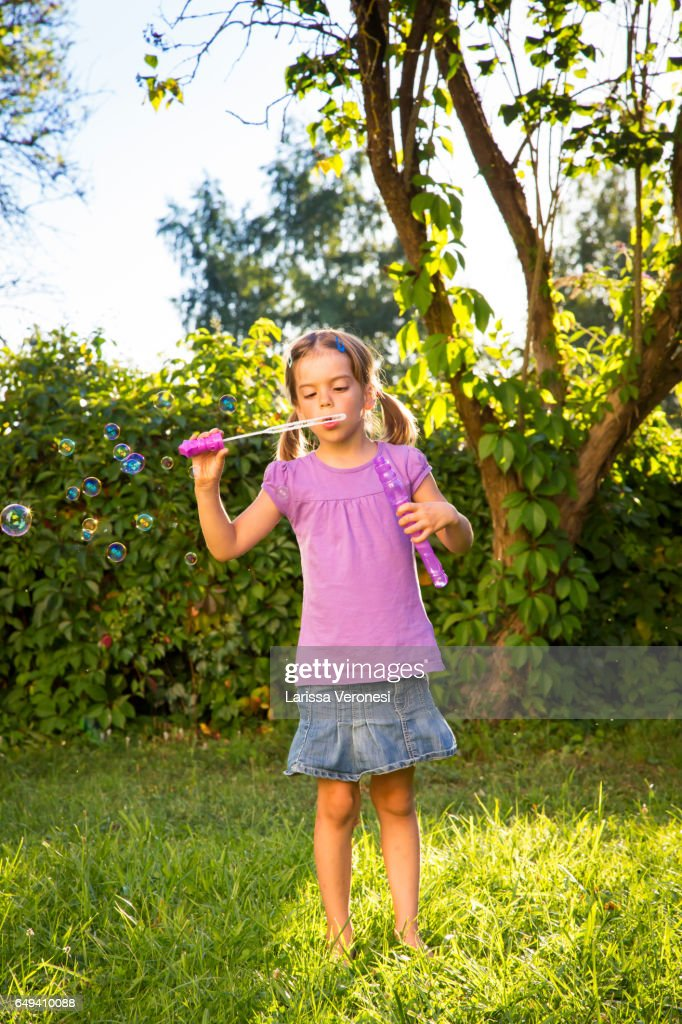 Little girl blowing soap bubbles on a meadow : Stock-Foto