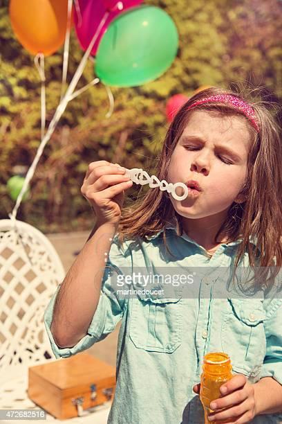 Little girl blowing soap bubbles outdoors in a kid party.
