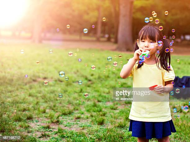 little girl blowing soap bubbles - beautiful japanese girls stock photos and pictures