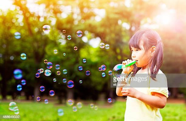 Little girl Soplando burbujas de jabón