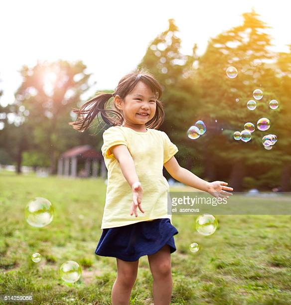 little girl blowing soap bubbles - cute little asian girls stock photos and pictures