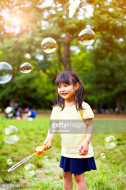 吹く液体石鹸の泡少女