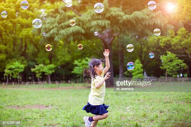 Kleines Mädchen blowing soap bubbles