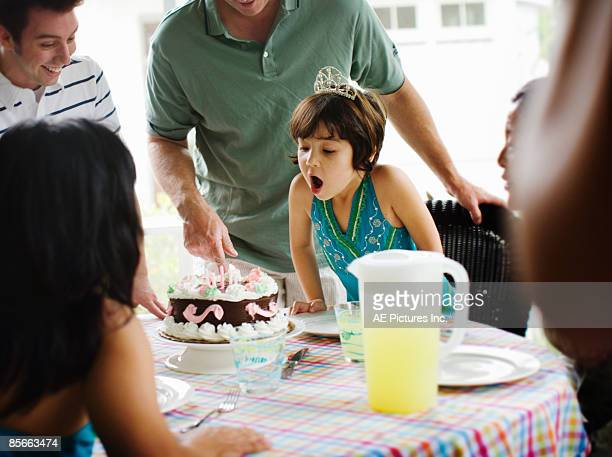Little girl blows out birthday candles