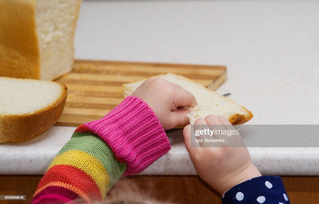 little girl breaks bread on a close-up table : Stock Photo