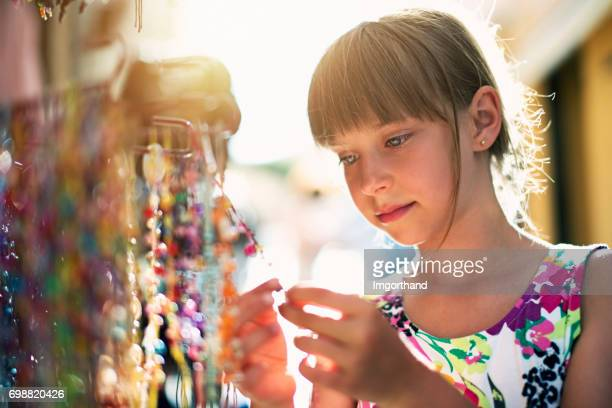 Little girl browsing colorful necklaces on souvenir street stand