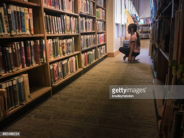 Little girl browsing for a book in library