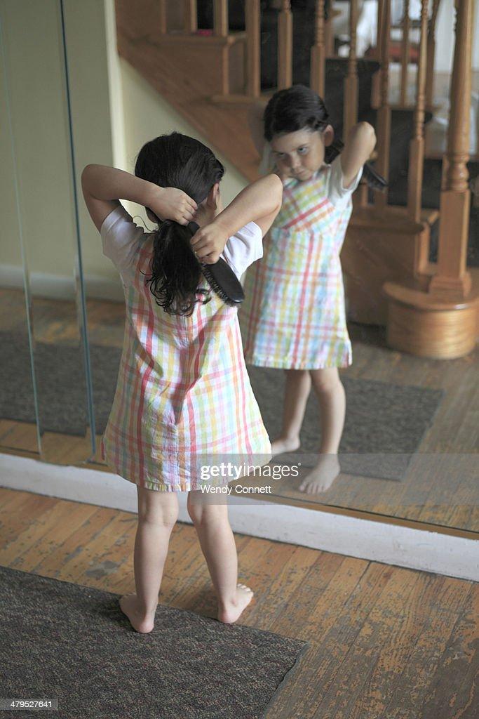 Little girl brushing hair : Stock Photo