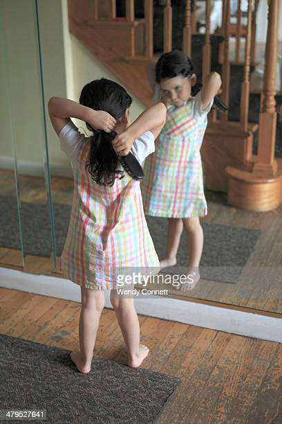 little girl brushing hair - girl in mirror stock photos and pictures
