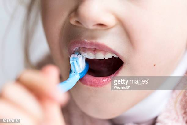 Little girl brushing her milk teeth, close-up