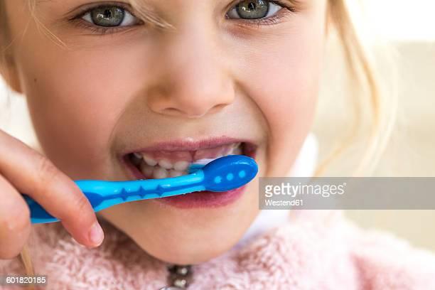 Little girl brushing her milk teeth, close-up