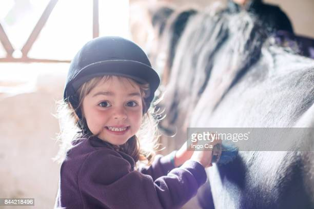 Little girl brushing her pony
