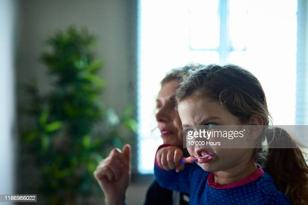 little girl brushing her teeth - advice stock pictures, royalty-free photos & images