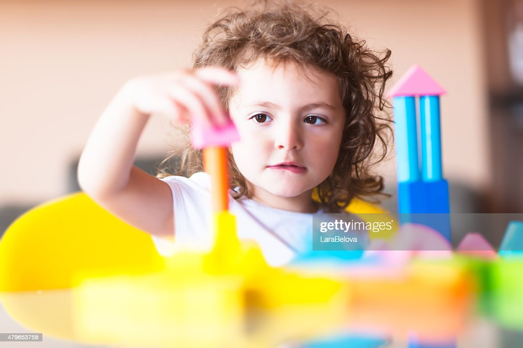 Little girl building a house with cubes : Stock Photo