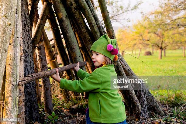 Little girl building a hut with logs on a meadow in autumn
