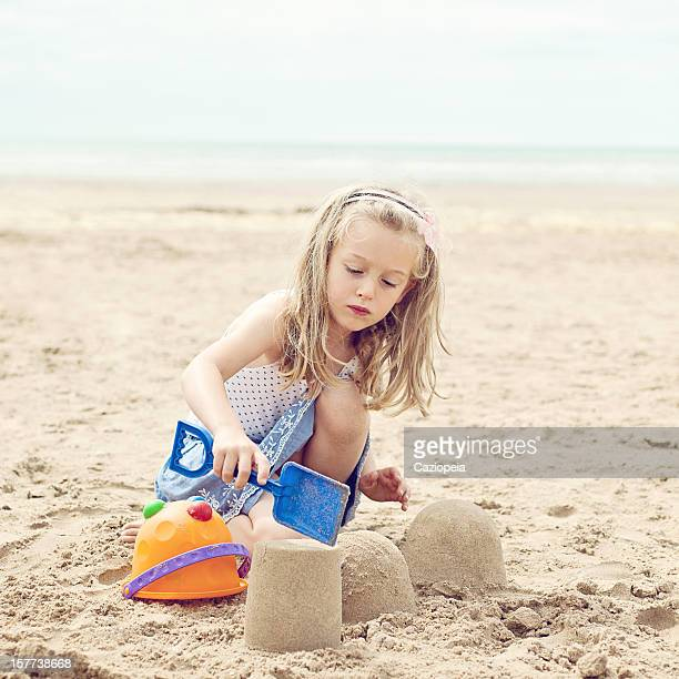 little girl building sand castles on beach - camber sands stock photos and pictures