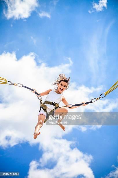Kleines Mädchen bungee-jumping auf Trampolin