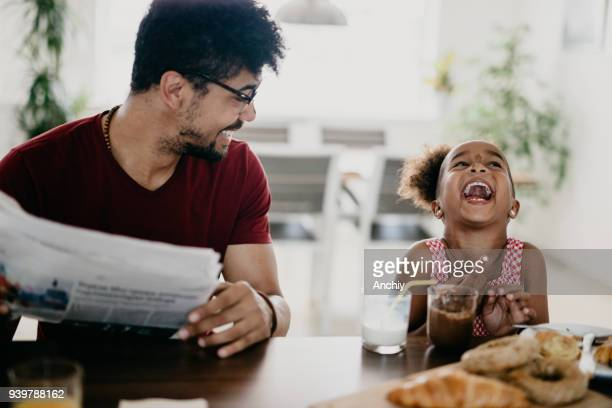 little girl bursts into laugh while having breakfast with her father - african american family home stock photos and pictures