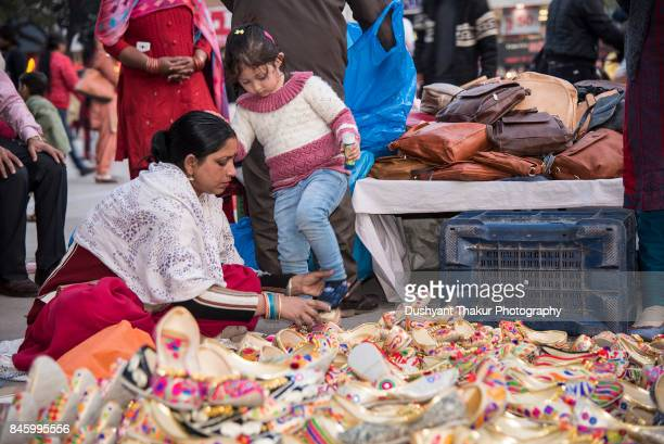 Little girl buying shoes in a local market.