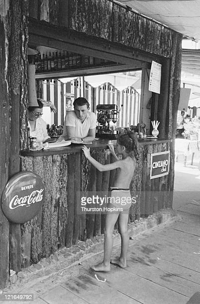 A little girl buys a drink at a bar on Paraggi Beach near the tourist resort of Portofino Italy August 1952 Original Publication Picture Post 6023...