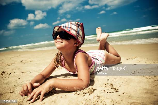 little girl by the sea - little girl laying on the beach stock photos and pictures