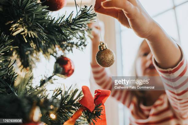 little girl carefully places christmas baubles onto a christmas tree - symbolism stock pictures, royalty-free photos & images