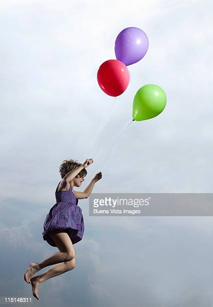Little girl carried in air by balloons