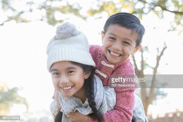 Little girl carries friend piggy back outside