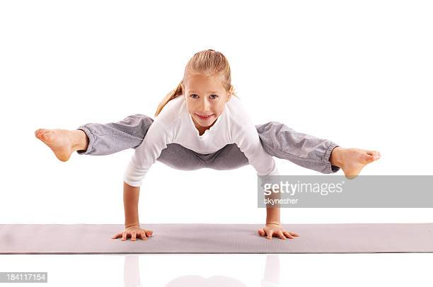 Little girl carries out gymnastic exercises.