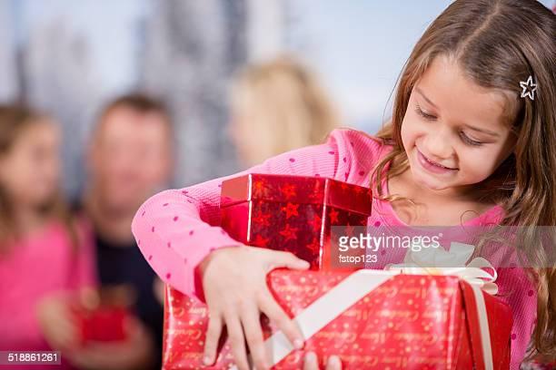 Petite fille de transporter une pile de cadeaux de Noël.  Famille en arrière-plan.