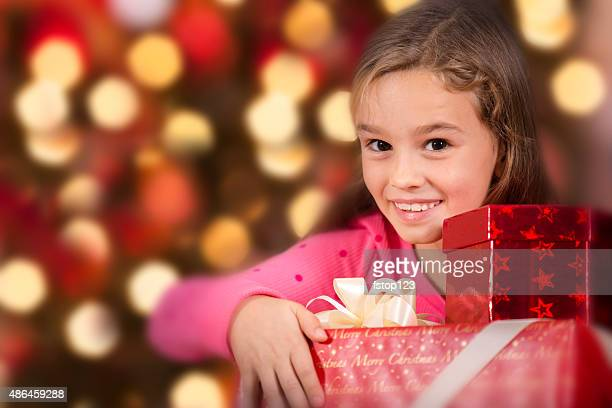little girl carries stack of christmas presents. tree background. - little girls giving head stock photos and pictures