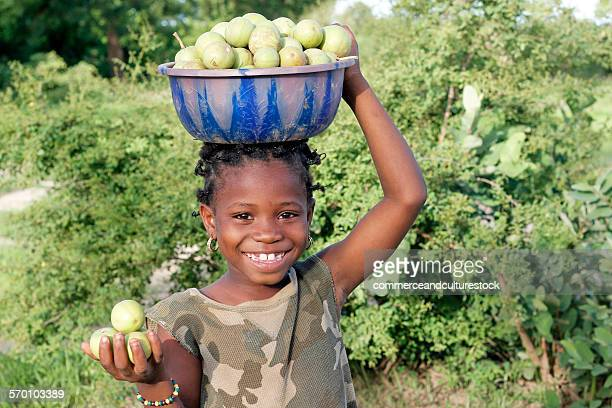 A little girl carrying a bucket of guavas