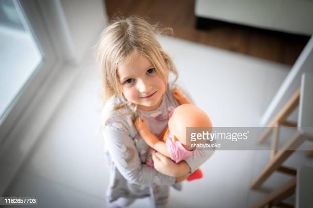 kleines mädchen trägt ihre liebevolle puppe - puppe stock-fotos und bilder