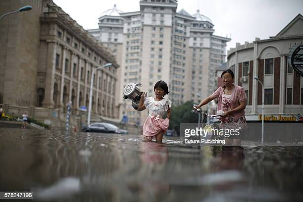 A little girl carrying two kettles walks around waterlogged street on July 20 2016 in Tianjin China Heavy rains hit Tianjin disrupting traffic in the...