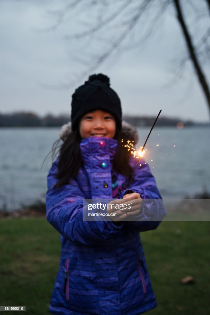 Little girl celebrating winter with sparklers outdoors at dusk : Stock Photo