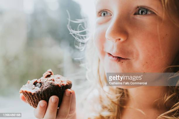 little girl chewing a chocolate chip bun - gluten free bread stock pictures, royalty-free photos & images