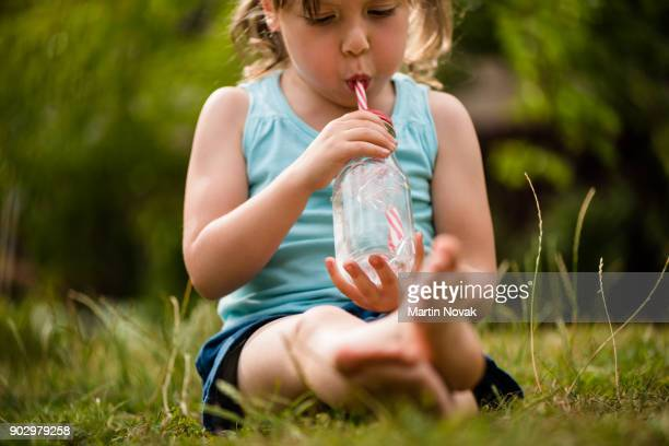 Little girl child in lawn sipping water