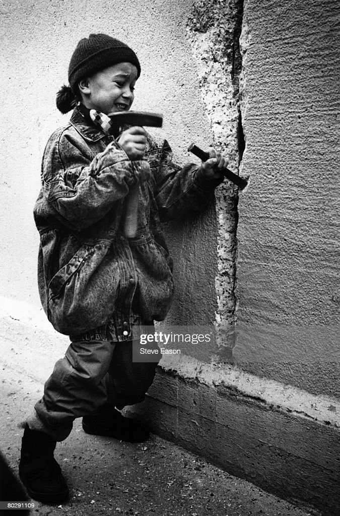 A little girl chisels away at the Berlin Wall from the east side on New Year's Eve, 31st December 1989.