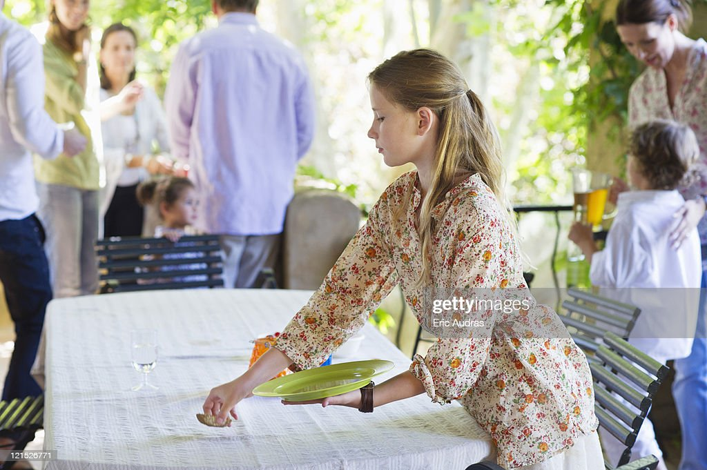 Little girl cleaning dining table after eating food with family in the background : Stock Photo